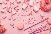Fotografie pohled shora sladký makronky, marshmallows a bonbóny izolovaných na růžové