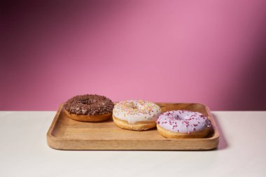 tasty donuts with icing on wooden cutting board on pink background