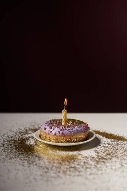 candle in middle of sweet donut with shiny sparkles on white table isolated on black