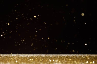 selective focus of golden sparkles falling on table isolated on black
