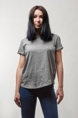 Photo beautiful young woman in grey t-shirt with copy space looking at camera isolated on white