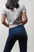 Photo back view of young woman in denim and white t-shirt with copy space isolated on white