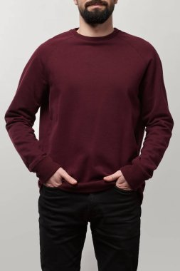 partial view of man with hands in pockets in burgundy sweatshirt with copy space isolated on grey