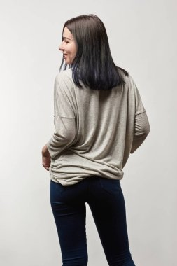 back view of young woman in grey long sleeve with copy space isolated on white