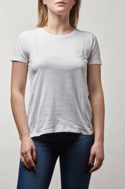 partial view of young woman in white t-shirt with copy space isolated on grey