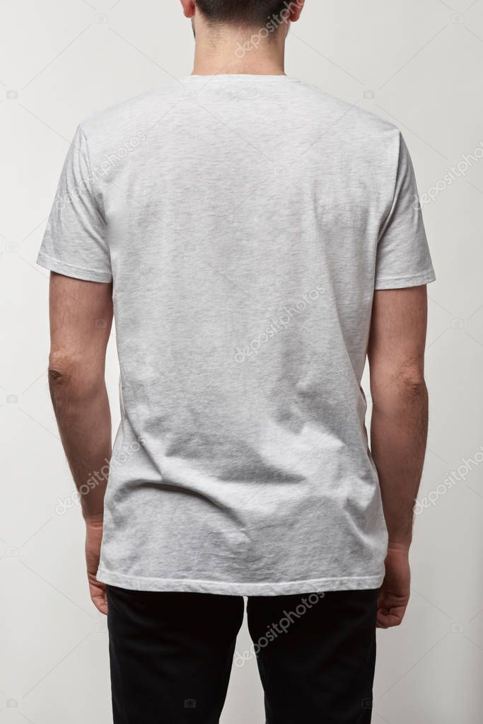 Back view of man in casual white t-shirt with copy space isolated on grey stock vector