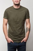 Photo partial view of tattooed man in khaki t-shirt with copy space isolated on grey