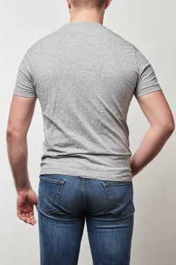 Back view of man in denim and t-shirt with copy space isolated on grey stock vector