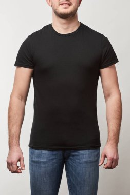 Partial view of man in denim and black t-shirt with copy space isolated on grey stock vector