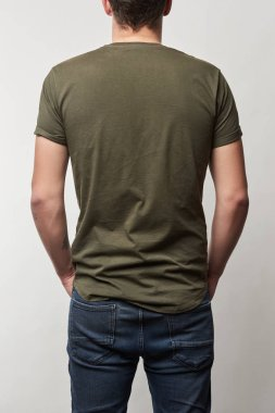 Back view of man in khaki t-shirt with copy space isolated on grey stock vector
