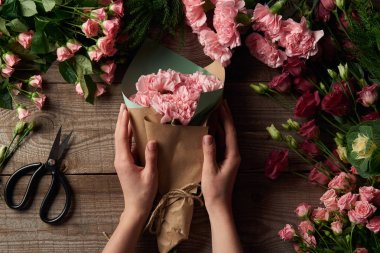 cropped shot of female hands holding beautiful bouquet and tender flowers with scissors on wooden surface