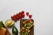 top view of toasts on wooden cutting boards with avocados and cherry tomatoes  on grey backgroud