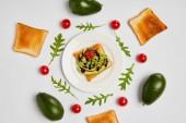 pohled shora toasty na desce s avokádo, cherry rajčátky a arugulas listy na šedém pozadí