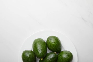 top view of avocados in plate on grey textured background