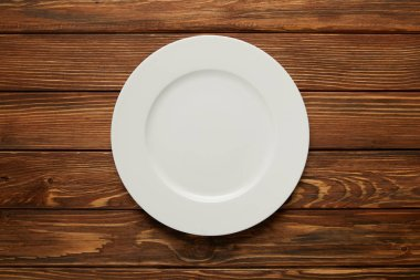 top view of white empty plate on wooden background