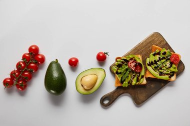 top view of toasts on wooden cutting board with avocados and cherry tomatoes on grey backgroud