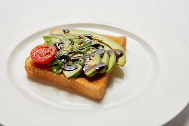 selective focus of toast with avocado and cherry tomato on white plate