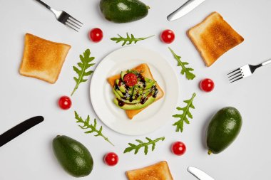 top view of toasts on plate with avocados, cherry tomatoes, arugulas leaves, forks and knives on grey background