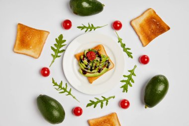 top view of toasts on plate with avocados, cherry tomatoes and arugulas leaves on grey background