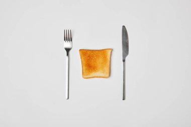 top view of grilled crispy toast with fork and knive on grey background