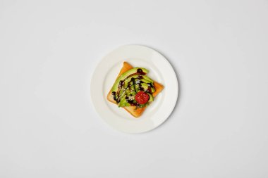 top view of toast in plate with avocado and cherry tomato on grey background