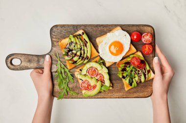 top view of womans hands holding wooden cutting board with toasts and scrambled egg on marble surface