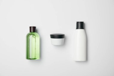 Top view of different cosmetic bottles on white background