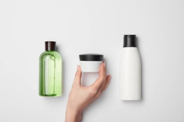 Top view of female hand near cream container with different cosmetic bottles on white background