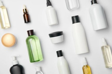 Top view of various cosmetic bottles and containers on white background