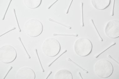 Top view of cotton cticks and cosmetic pads on white background