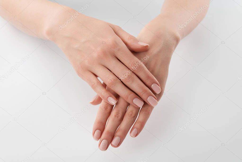 Partial view of female well-cared clanched hands on white background
