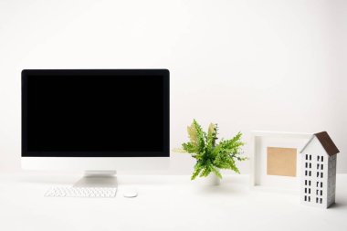 Workplace with plant, house model, photo frame and desktop computer with copy space isolated on white stock vector