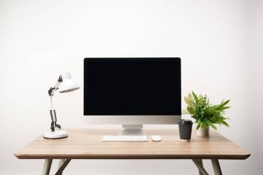 workplace with coffee to go, lamp, green plant and desktop computer with copy space isolated on white