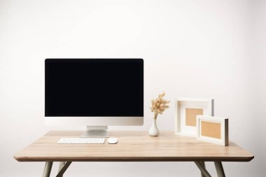 workplace with photo frames, dry flowers and desktop computer with copy space isolated on white