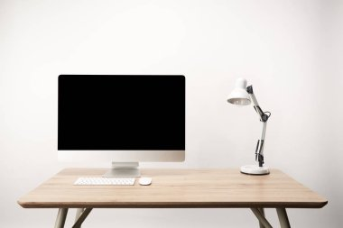 workplace with lamp and desktop computer with copy space isolated on white