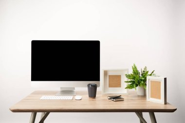 workplace with coffee to go, photo frames, plant and desktop computer with copy space isolated on white