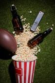 Fotografia vista superiore di bottiglie marroni vicino popcorn, telecomando e sfera che si trova sullerba
