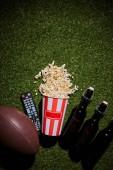 Fotografia vista superiore di bottiglie di birra nei pressi di popcorn, telecomando e sfera che si trova sullerba