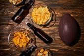 Fotografia vista superiore di snack in ciotole vicino bottiglie marroni con birra e palla sulla tavola di legno