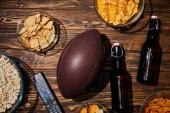 Fotografia vista superiore di snack in ciotole vicino bottiglie marroni con birra e palla sul tavolo in legno