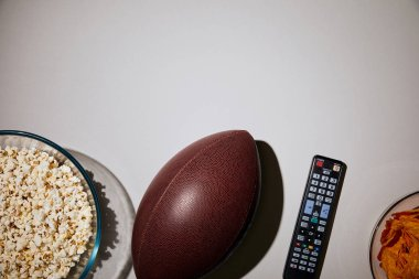 top view of popcorn in bowl near ball and remote control on white background