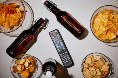 top view of brown bottles with beer near snacks in bowls and remote control on white background
