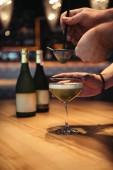 Fotografie částečný pohled barmani přípravě alkoholických koktejlů pomocí síta na dřevěný stůl v barech