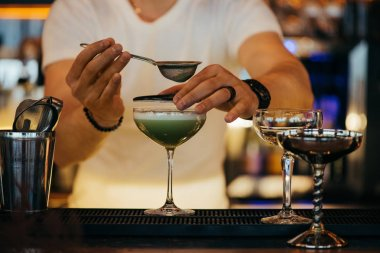 selective focus of bartender preparing alcoholic cocktail using sieve