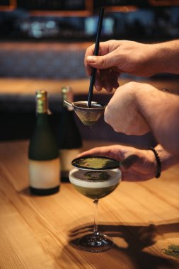 partial view of bartenders preparing alcoholic cocktail using sieve on wooden table in bar