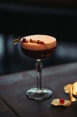 Fotografia fuoco selettivo del delizioso cocktail alcolico con schiuma e fiori secchi su sfondo scuro