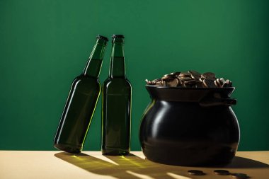 beer bottles and black pot with golden coins isolated on green, st patrick day concept