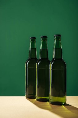 beer bottles with shadows isolated on green, st patrick day concept