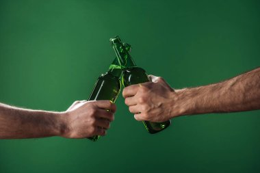 partial view of men clinking beer bottles isolated on green, st patrick day concept