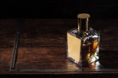 bottle of luxury alcohol with blank label on brown wooden table